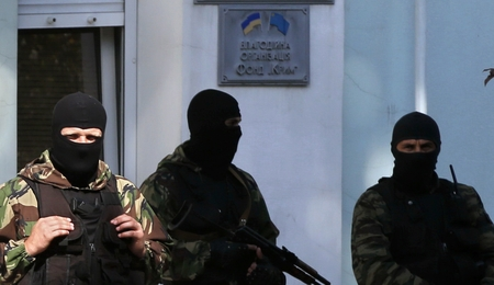 "Armed men stand guard in front of the entrance of the Mejlis of the Crimean Tatar people (the single highest executive-representative body of the Crimean Tatars) in Simferopol on September 16, 2014. Russian police on September 16 raided the assembly of pro-Kiev Crimean Tatars, activists told AFP, days after Crimean residents overwhelmingly backed pro-Kremlin parties in polls. Authorities also raided the homes of two Tatar activists in what the leader of the Tatar governing body, the Mejlis, called the start of ""direct repressions"" against the peninsula's pro-Kiev community. AFP PHOTO / MAX VETROV (Photo credit should read MAX VETROV/AFP/Getty Images)"